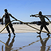 Air force personnel on a runway carrying firehoses.