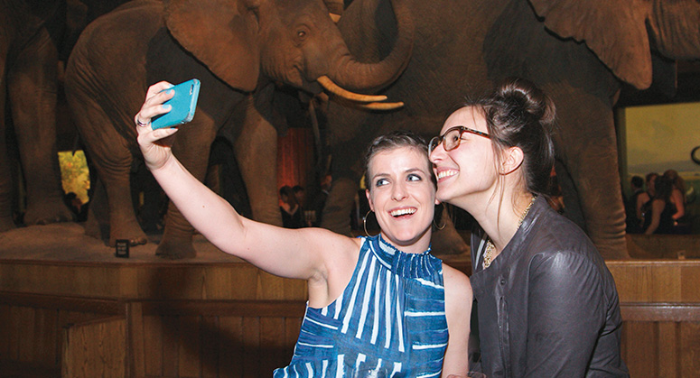 Students taking a selfie in front of wolly mammoths at the American Museum of Natural History