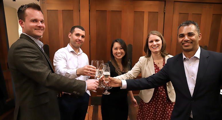Graduating members of the first Masters in Cybersecurity Risk and Strategy class celebrating with a champagne toast