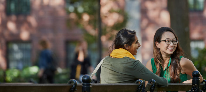 Two students on a bench in Washington Square Park