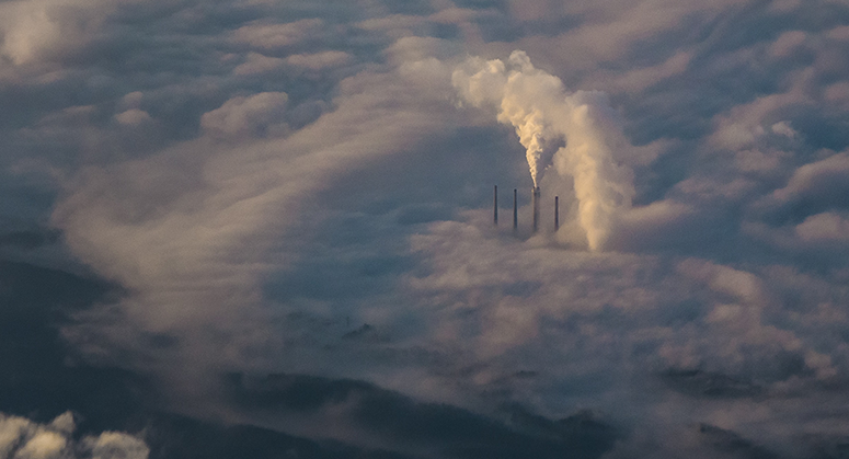 Plumes of emissions rise from four smokestacks.