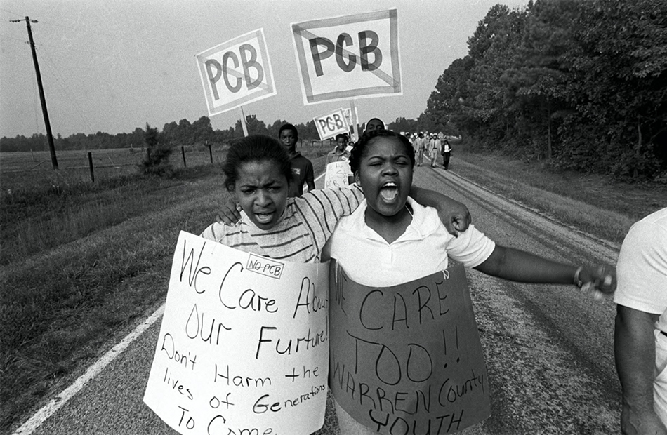 Two protesters carrying signs, protesting a chemical facility.