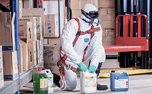 A man wearing protective equipment while handling containers of chemicals.