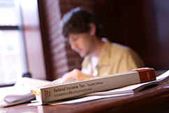 student studying with a tax study guide in the foreground