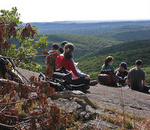 students sitting on rock bluff in Bear Mountain State Park