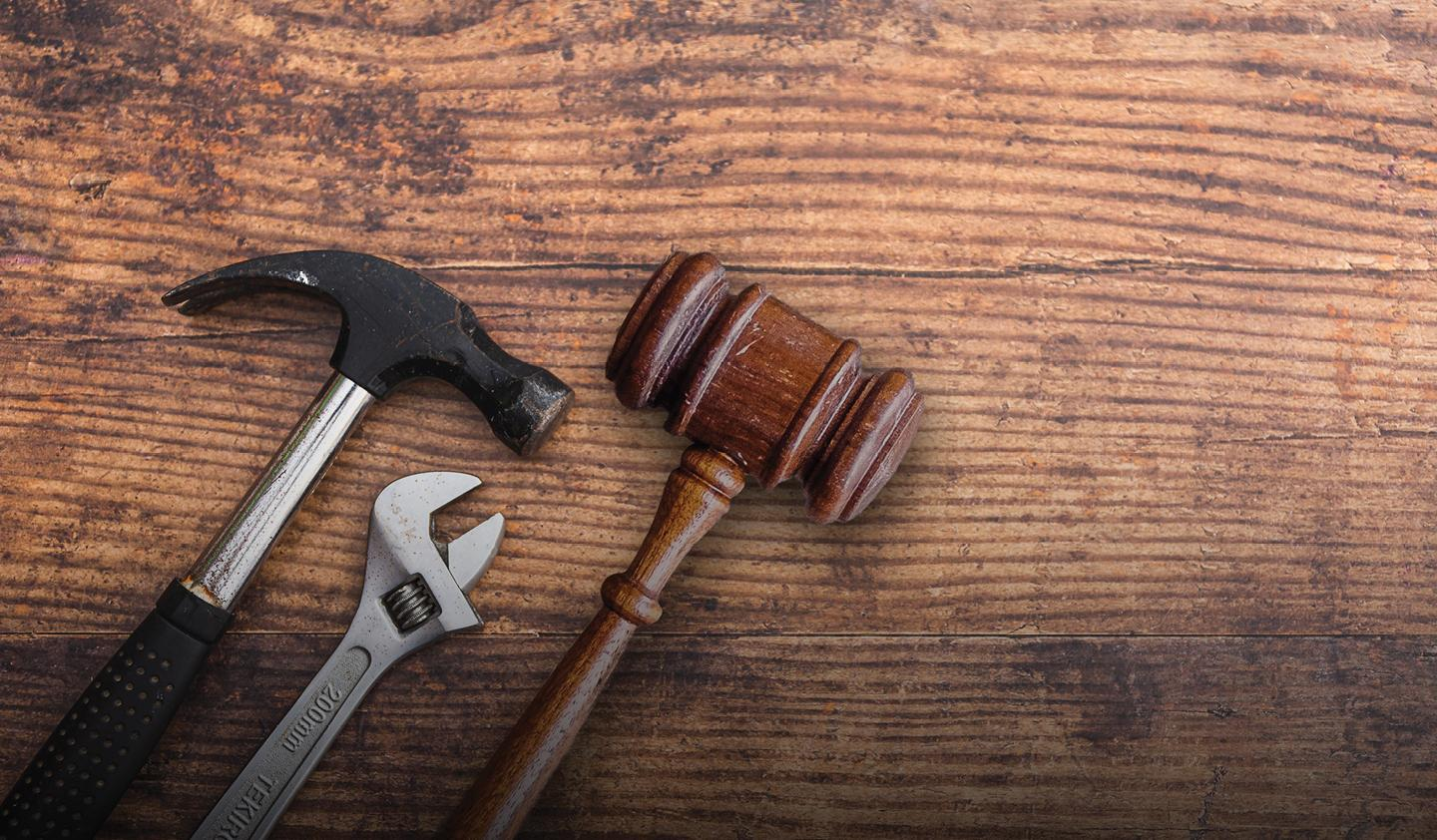 Hammer, wrench, and gavel on wooden surface