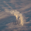 Emissions rising from smokestacks above a sea of clouds.