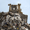 A bulldozer behind a pile of garbage at a landfill.