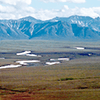 A photo of the Arctic National Wildlife Refuge with flat plains in the foreground and mountains in the background.
