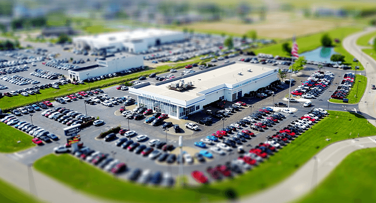 An aerial photo of a car dealership, showing parking lots filled with vehicles.